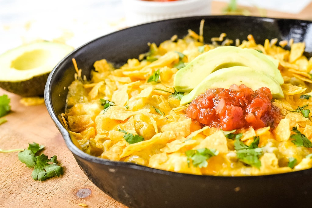 green chili egg casserole topped with tortilla chips avocado and salsa