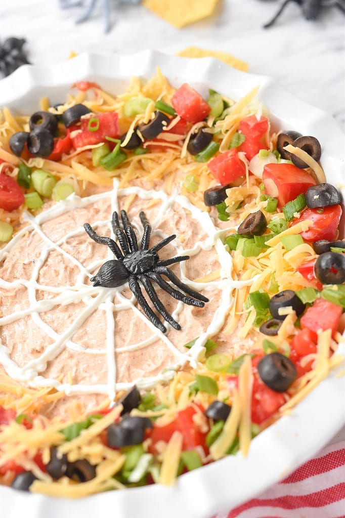 black plastic spider on a sour cream spider web 7 layer dip