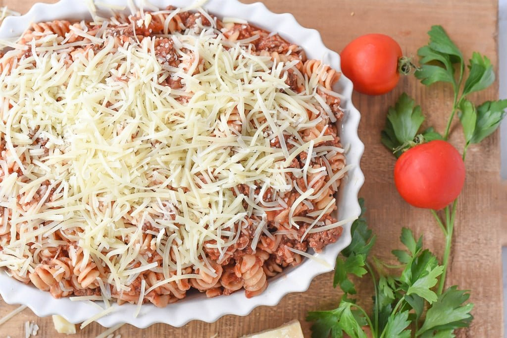 fussili pasta and meat sauce covered in mozzarella cheese
