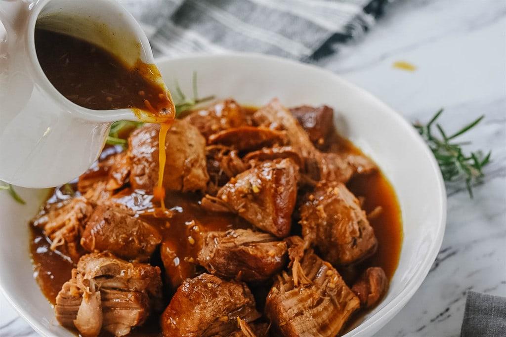 Pouring balsamic sauce over pork Tenderloin