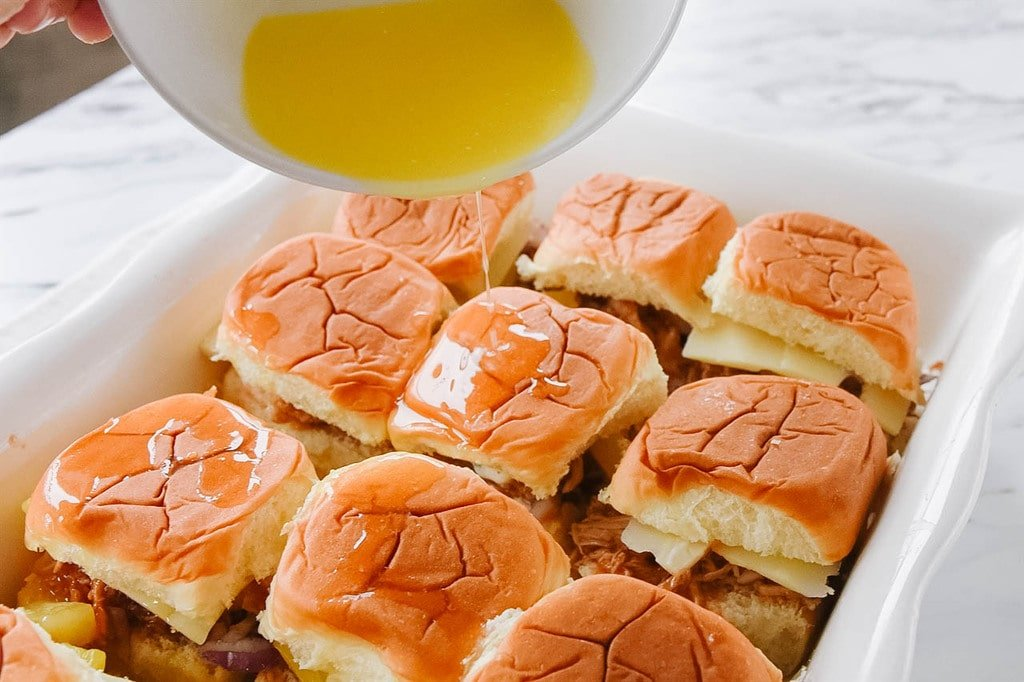 Pouring butter over Hawaiian Chicken Sliders