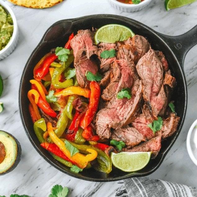 beef fajitas in a cast iron pan