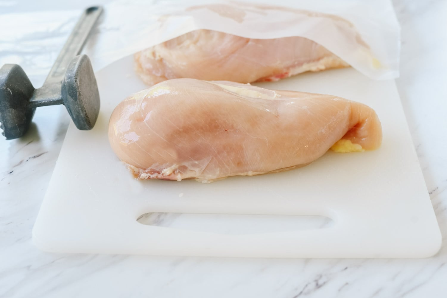 chicken breasts on cutting board