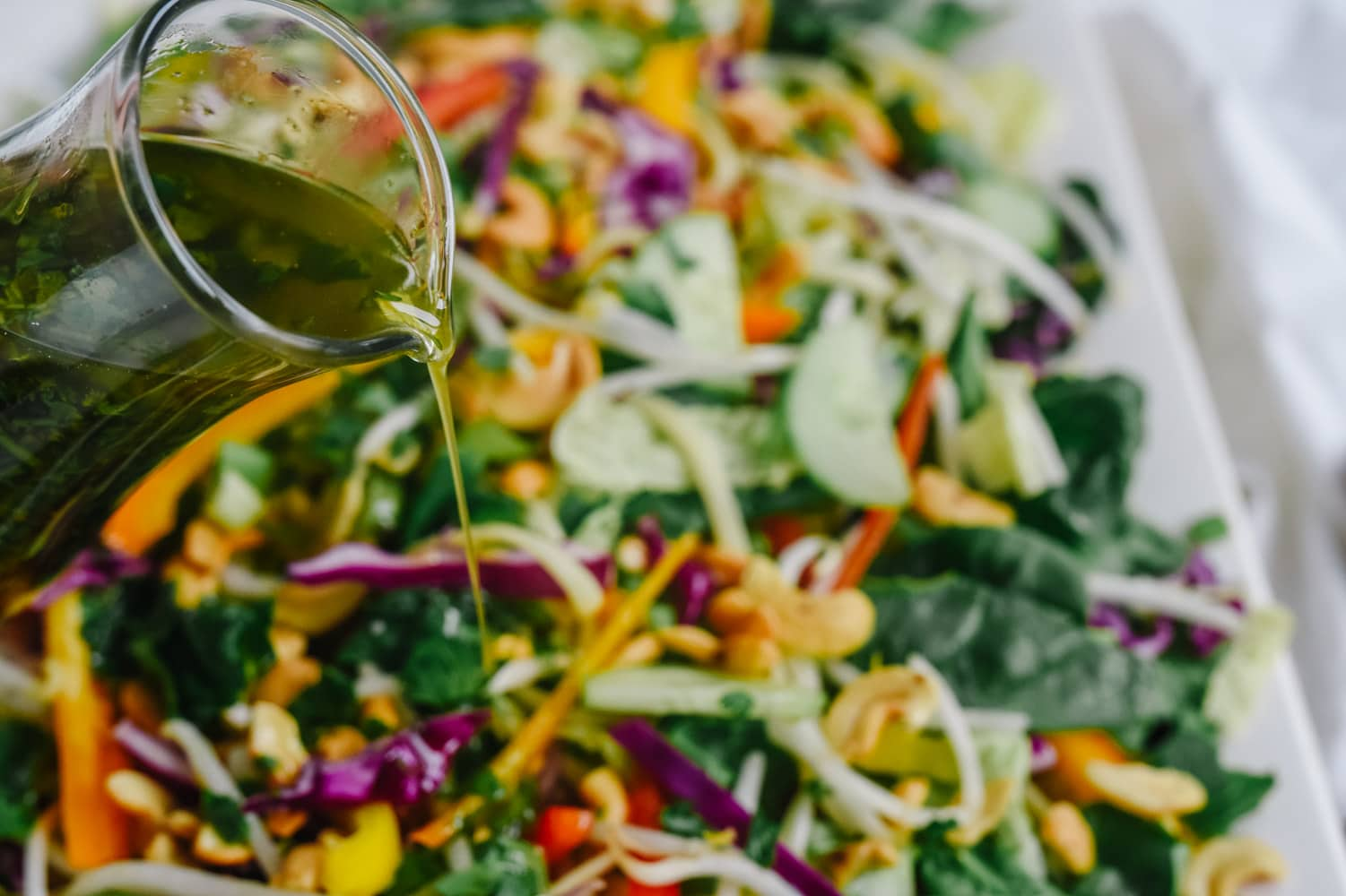 pouring dressing on asian noodle salad