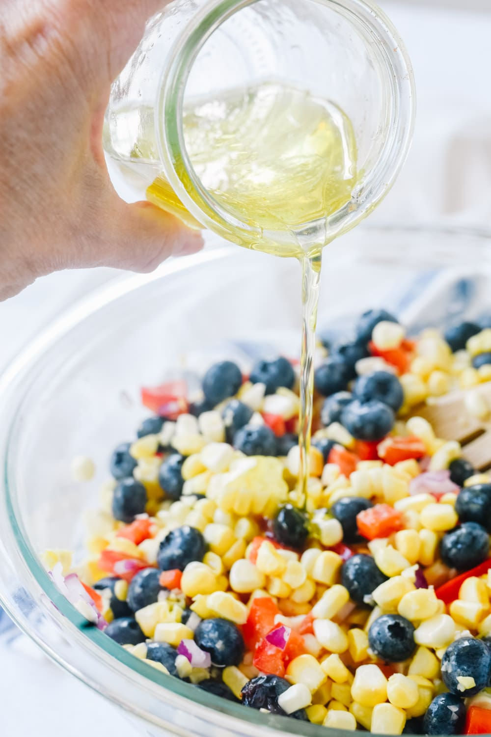 Pouring dressing on Blueberry Corn Salad