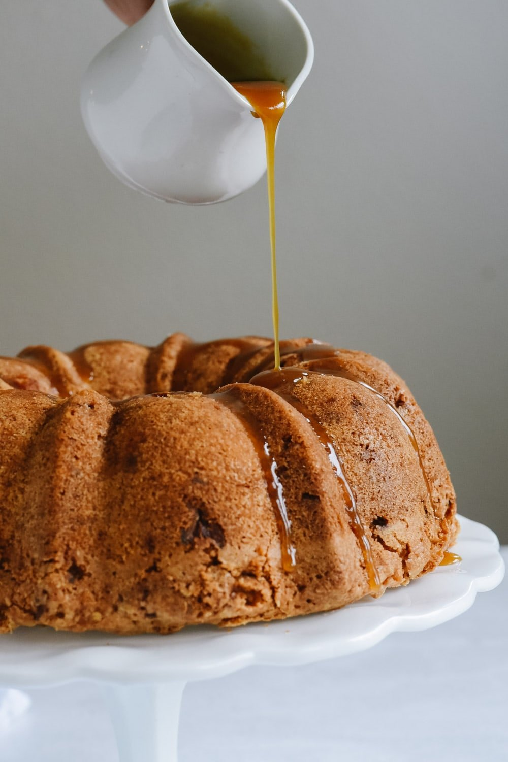 pouring caramel over apple bundt cake