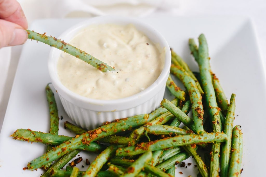 dipping pan seared green beans into a remoulade sauce