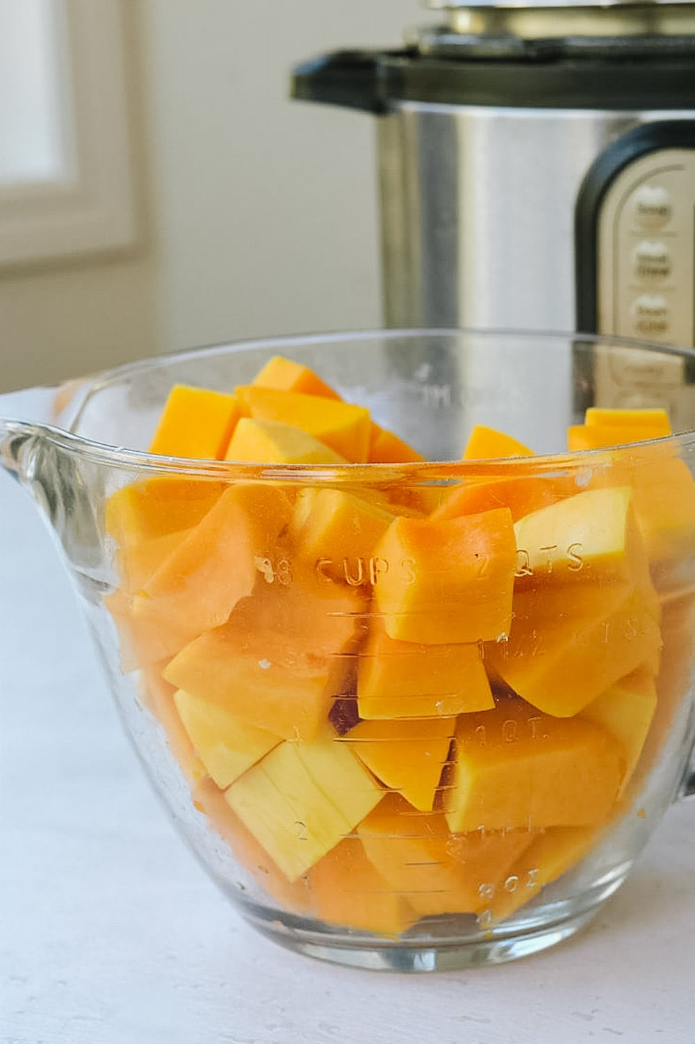 Cubed butternut squash in measuring cup