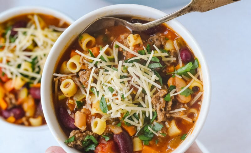 hand holding bowl of pasta e fagioli