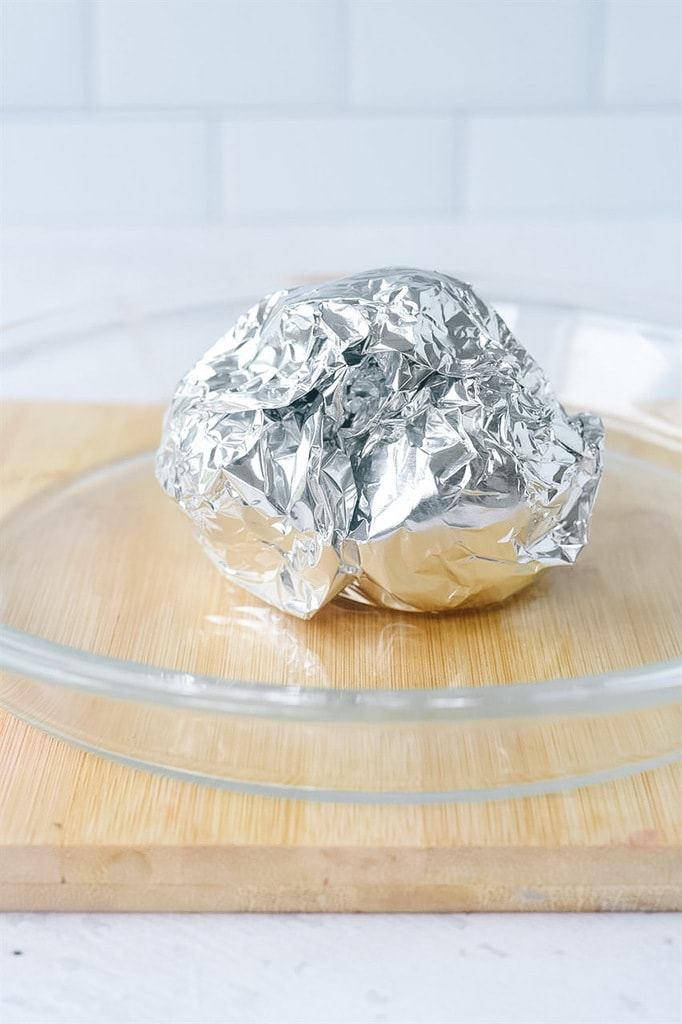 Roasted garlic covered with foil.