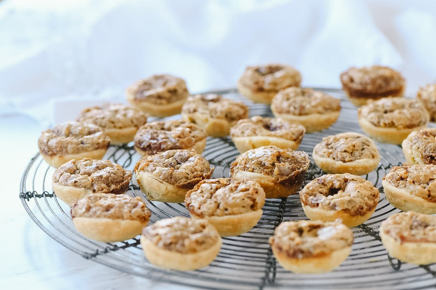 pecan tassies on a cooling rack.