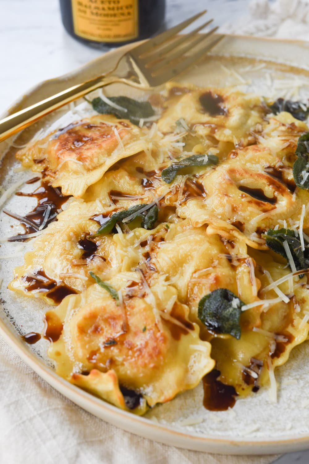 brown butter ravioli on a plate with sage