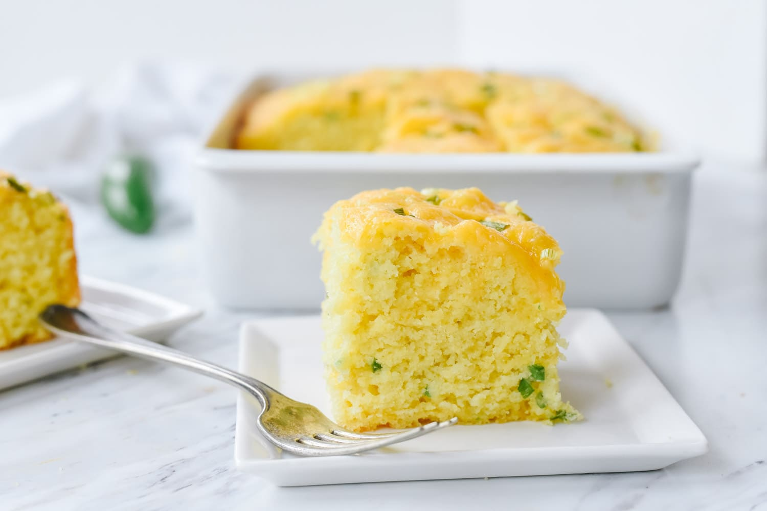 slice of jalapeno cornbread on a white plate.