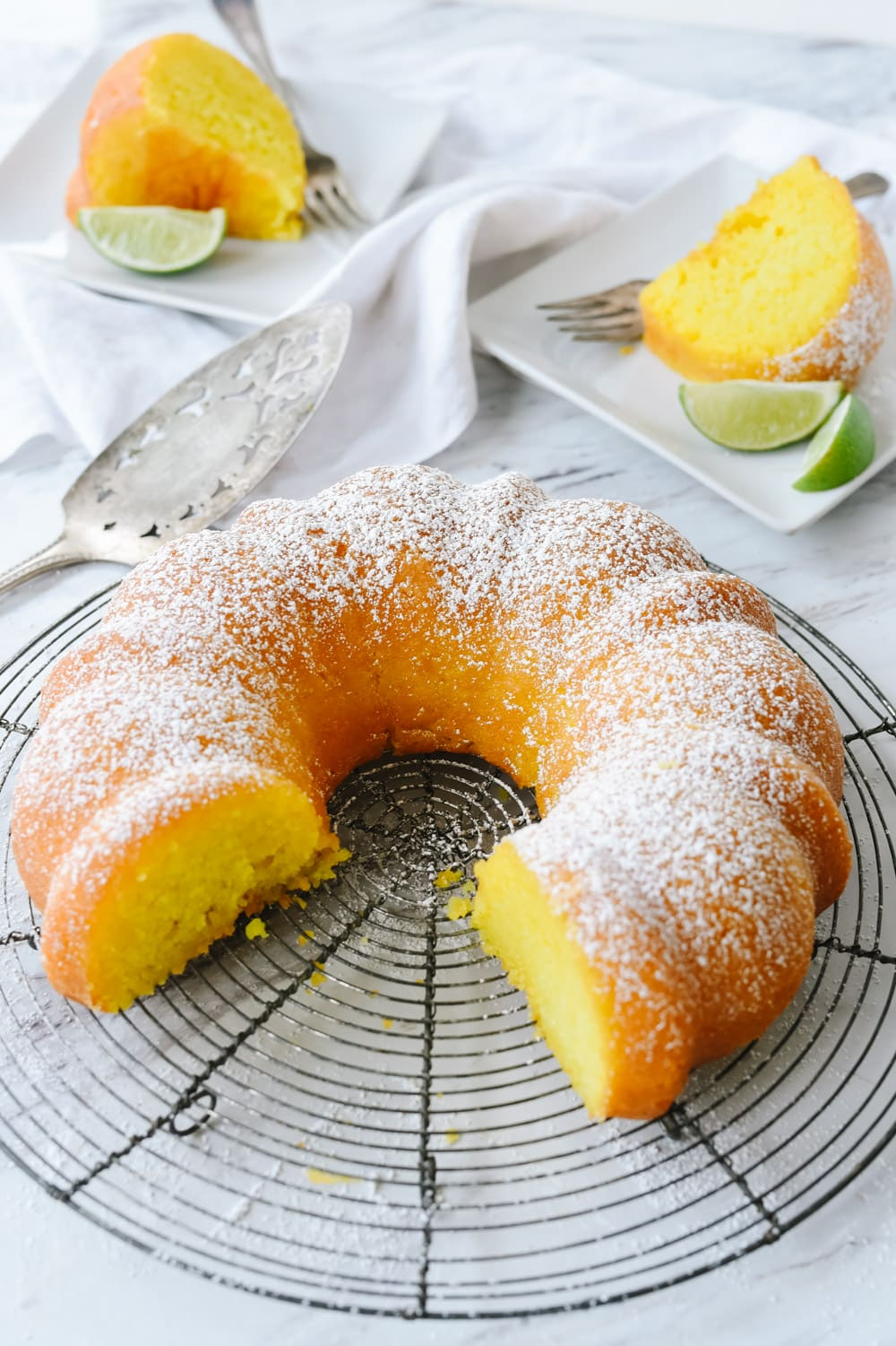 key lime cake with two pieces cut out of it
