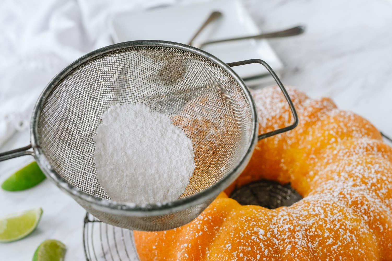 garnishing key lime cake with powdered sugar