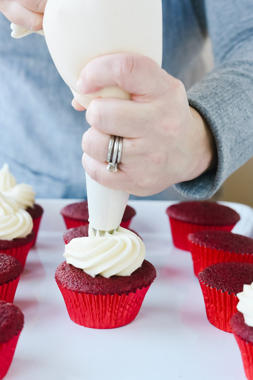 frosting a red velvet cupcake