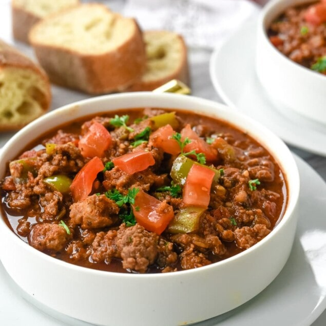 bowl of chili with tomatoes on top