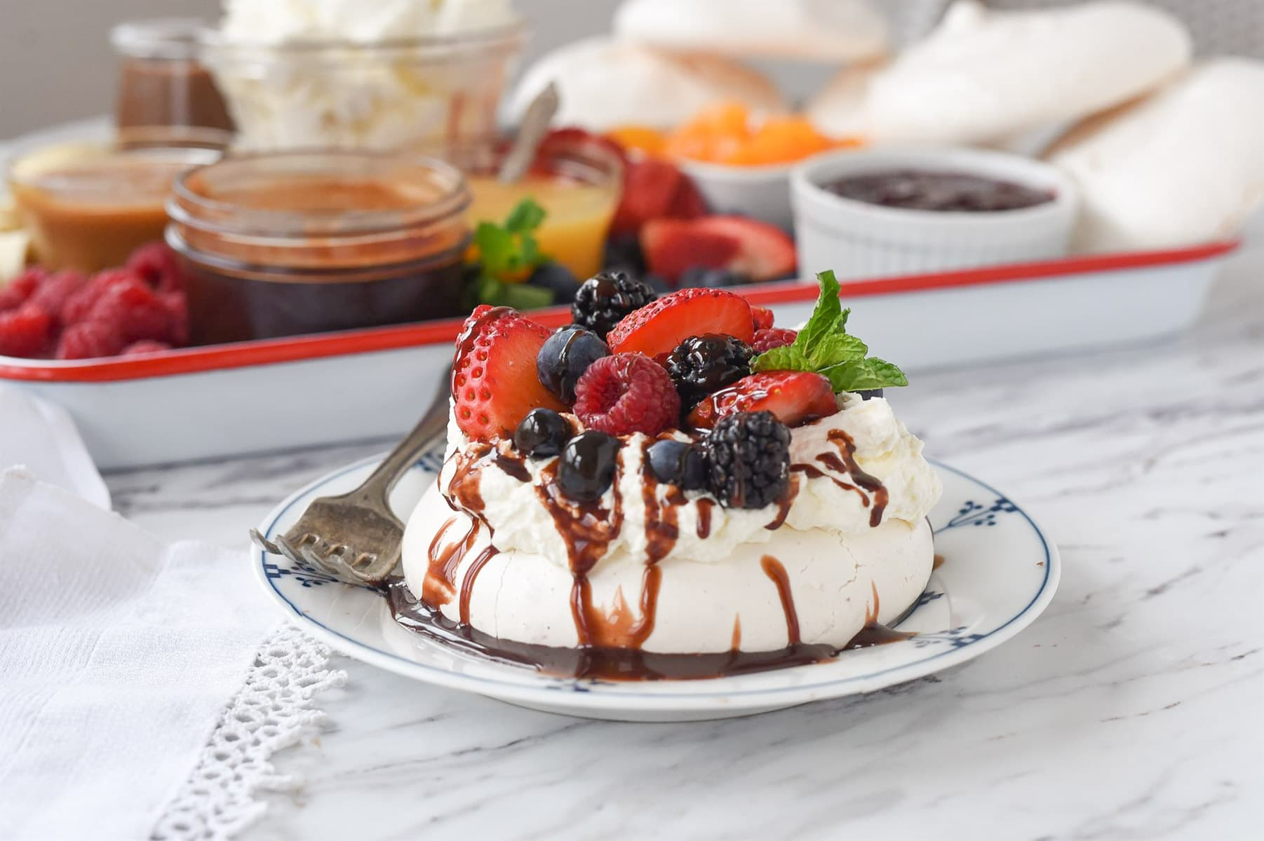 pavlova on a plate in front of dessert board
