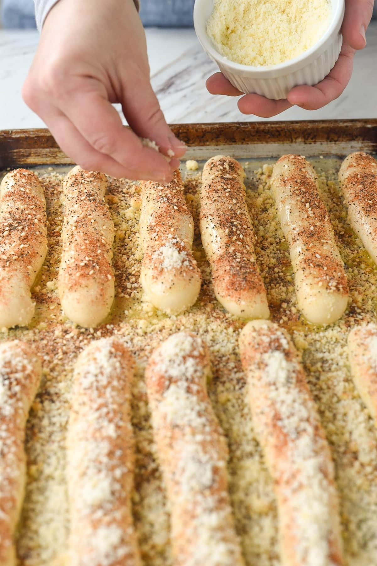 sprinkling cheese on breadsticks