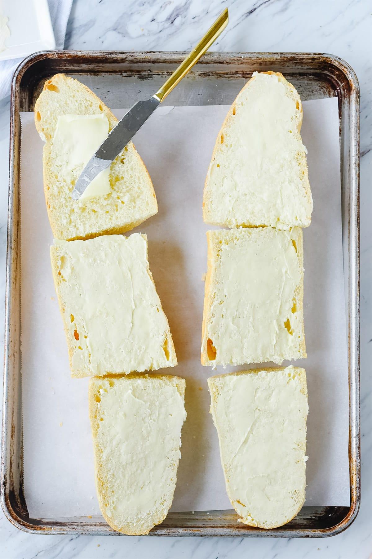 buttering garlic bread