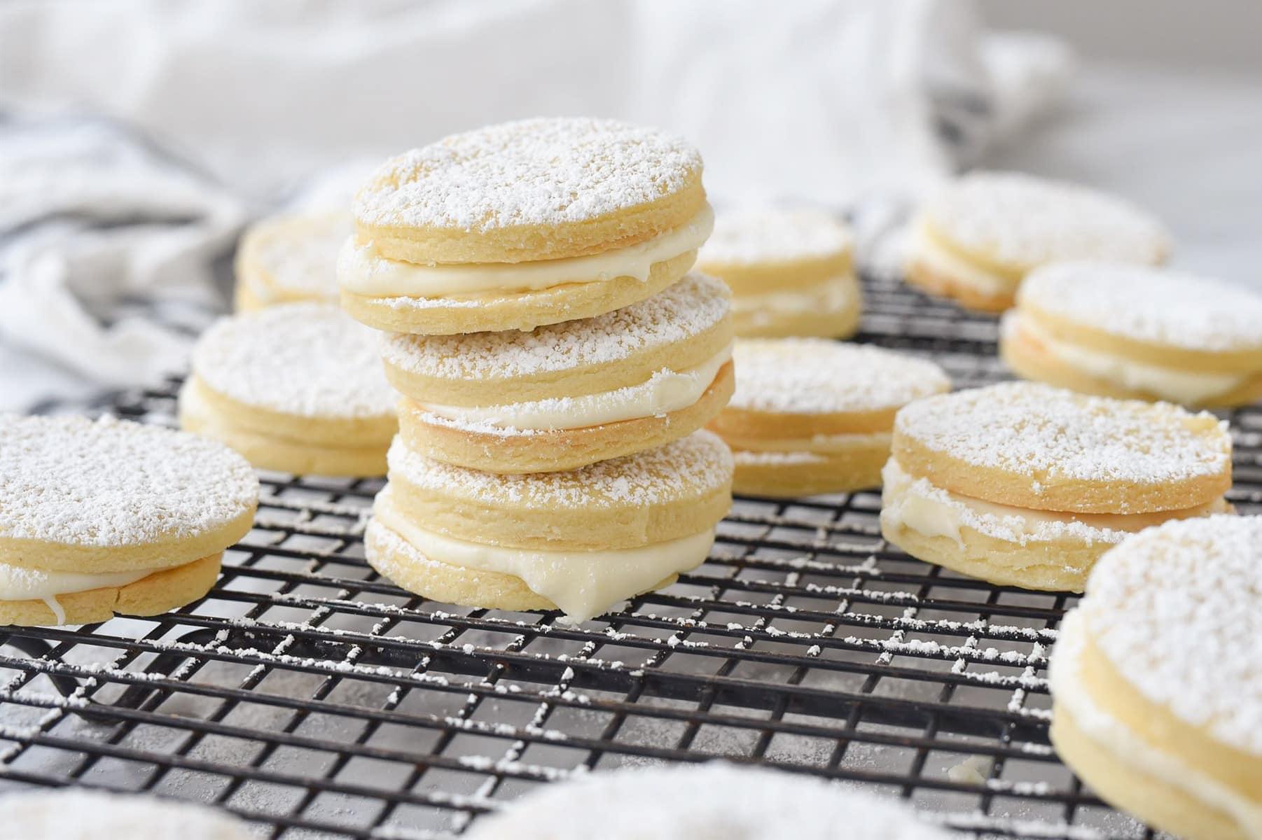 pile of lemon sandwich cookies on a cooling rack