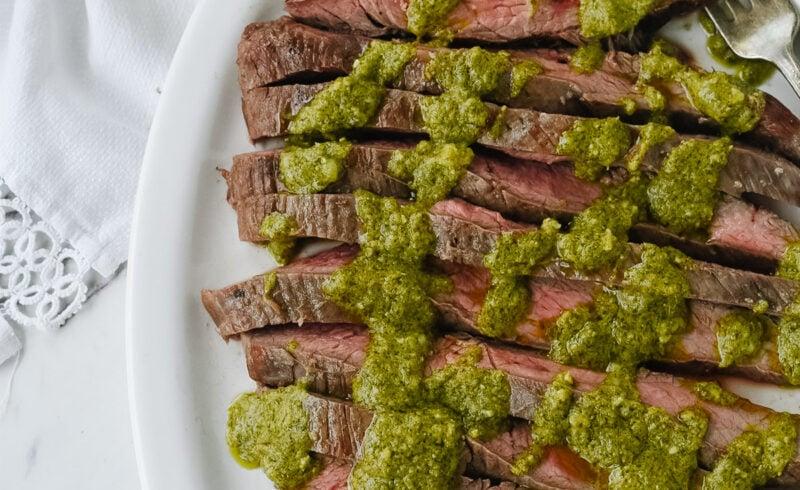 pesto flank steak on a white dish