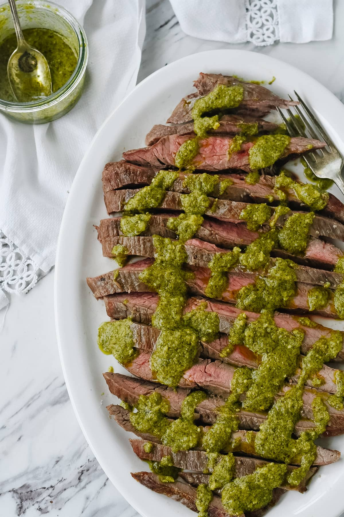 pesto flank steak on a white dish