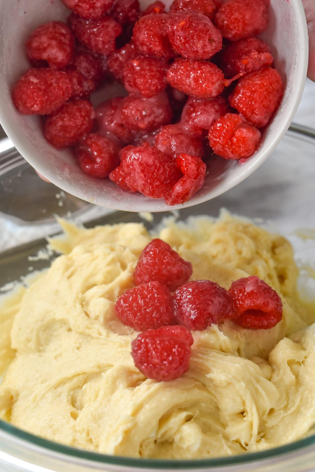adding raspberries to muffins