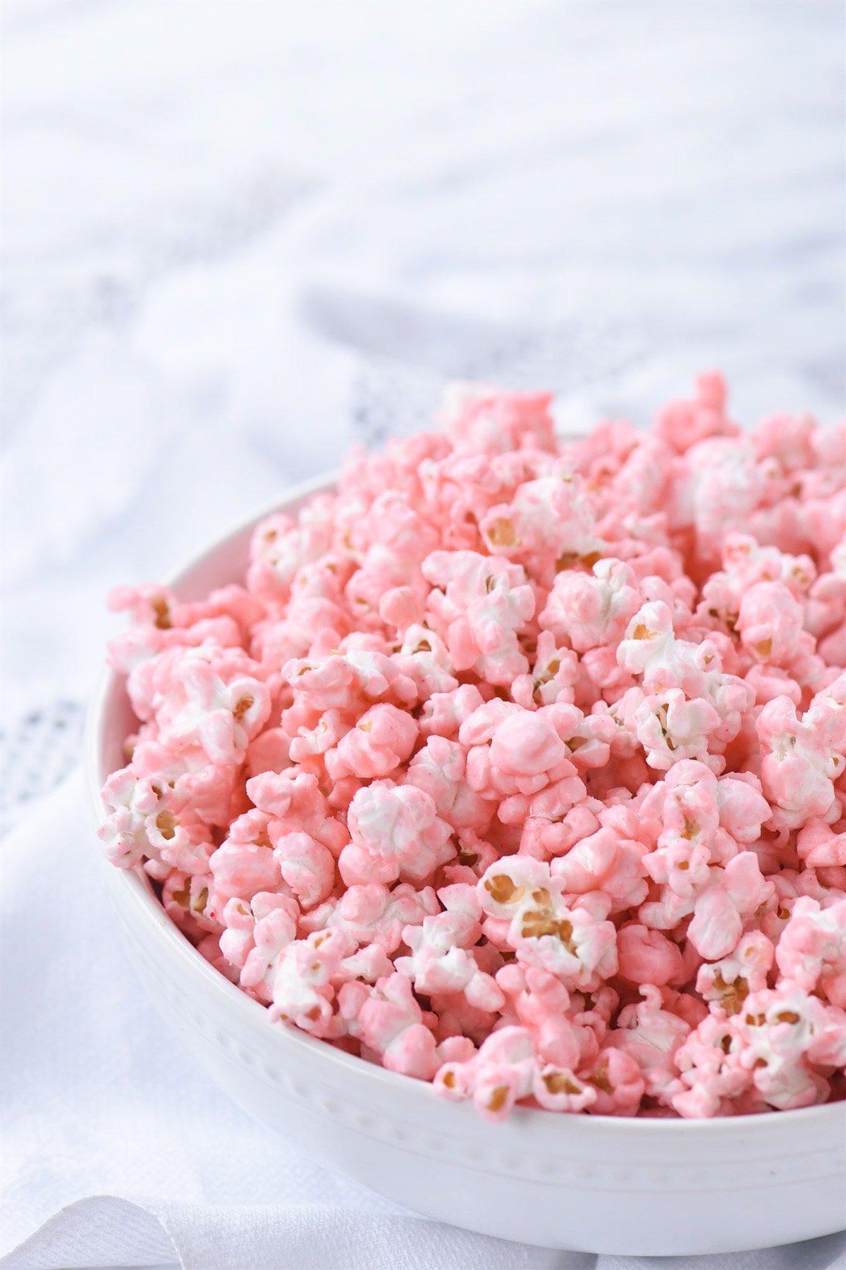 white bowl of pink popcorn