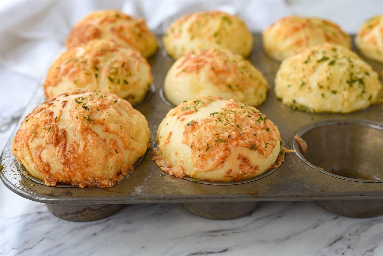 garlic parmesan rolls in a muffin tin
