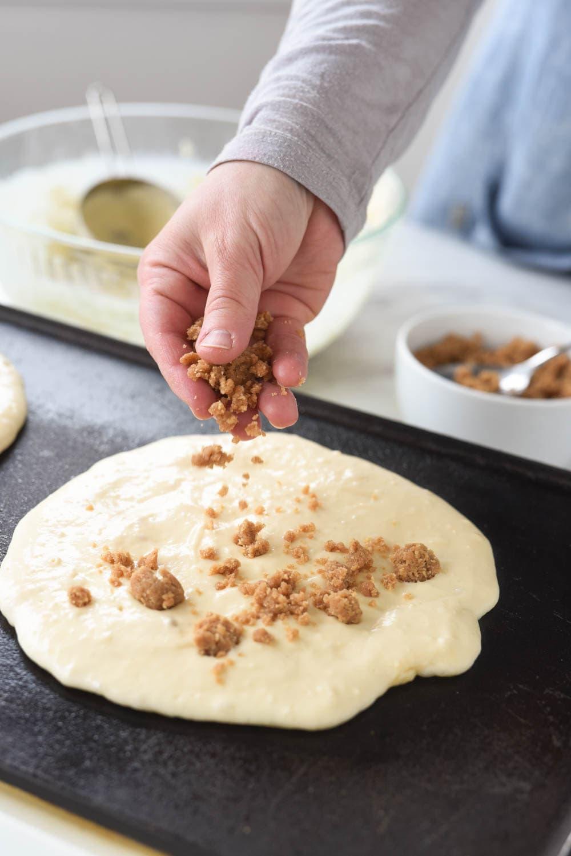 sprinkling streusel topping onto pancake
