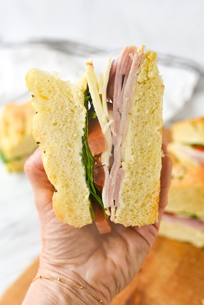 hand holding a piece of picnic sandwich