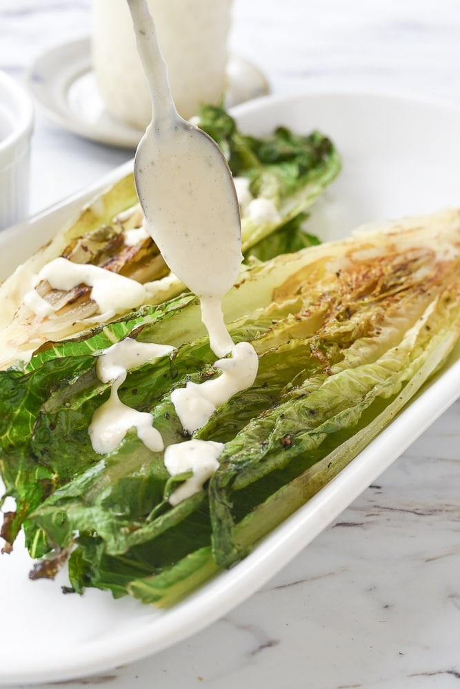 spooning caesar salad dressing on lettuce