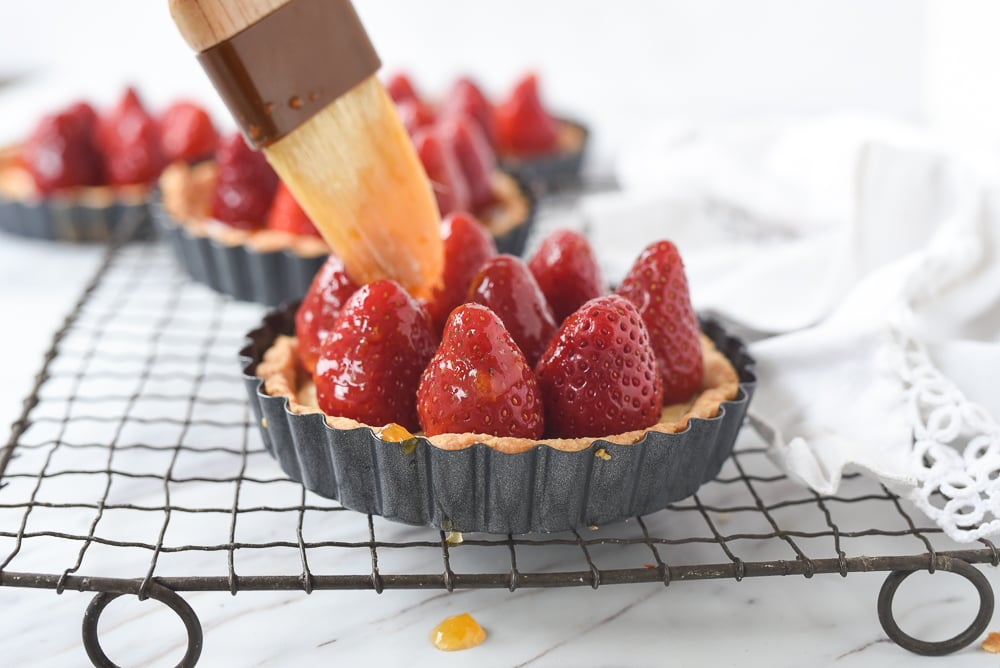 brushing glaze on strawberries
