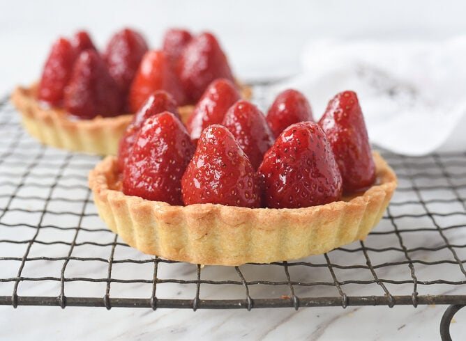two strawberry tarts on a cooling rack