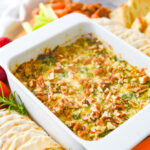 bowl of artichoke dip with pecans on top