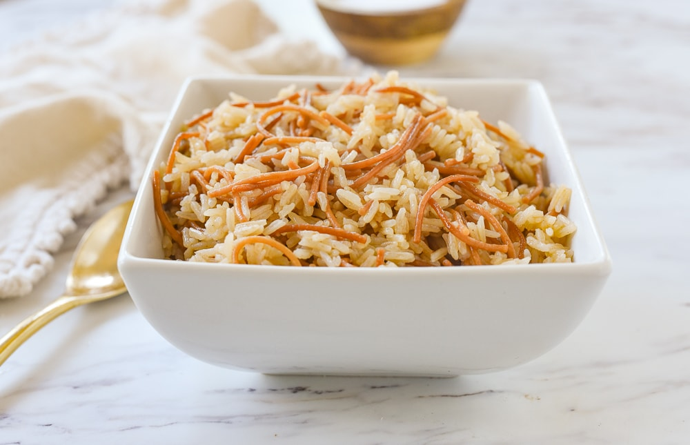 white bowl of rice pilaf with a spoon