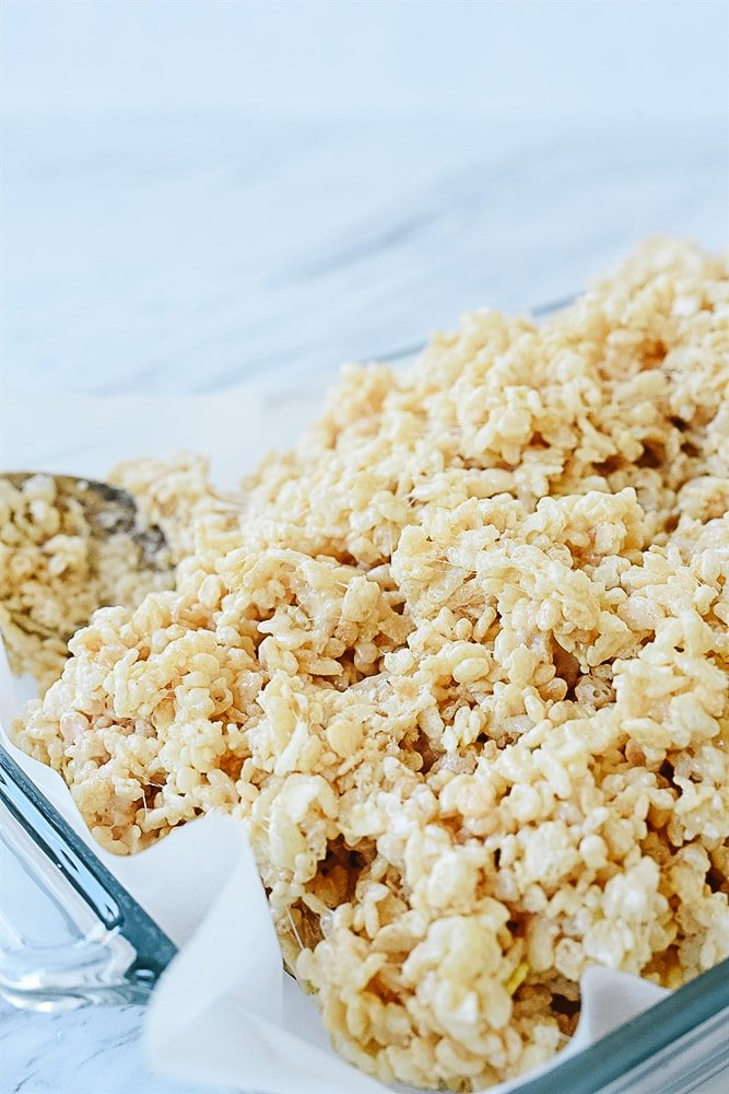 putting rice krispie treats is a pan.