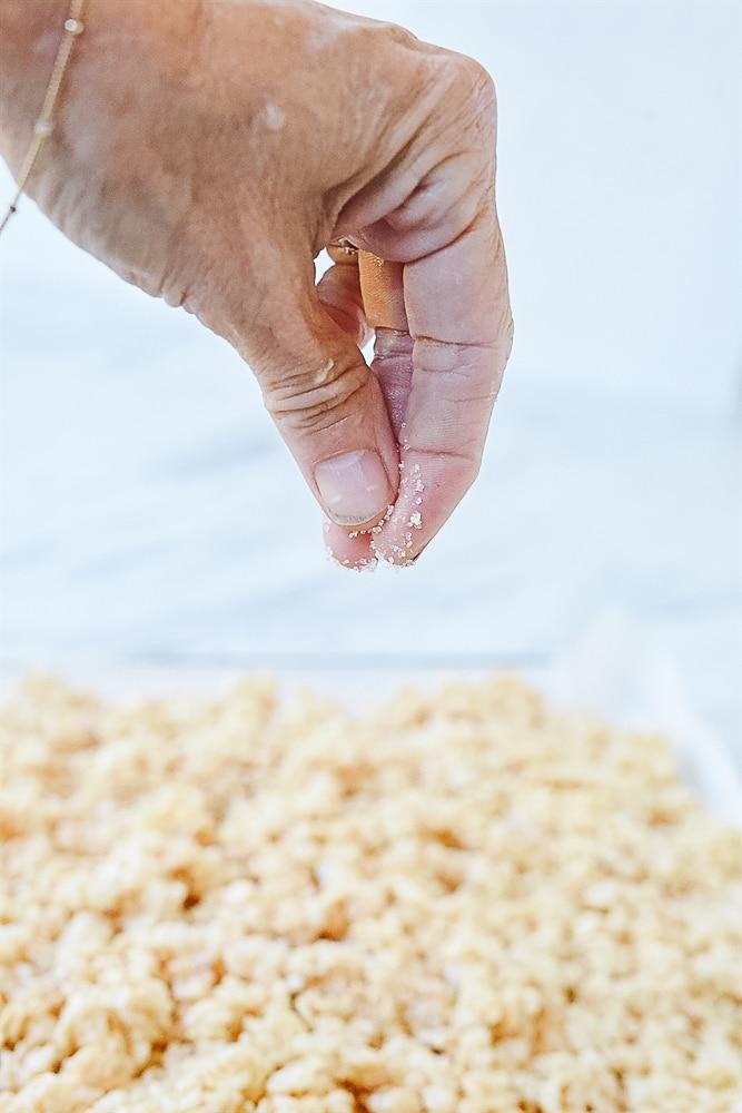 Sprinkling salt onto rice krispie treats.