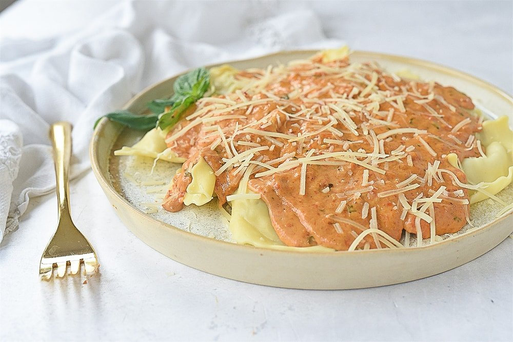 plated of red pepper cream sauce over ravioli