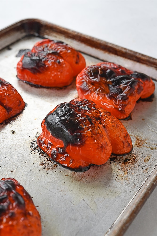 charred red pepper on a baking sheet