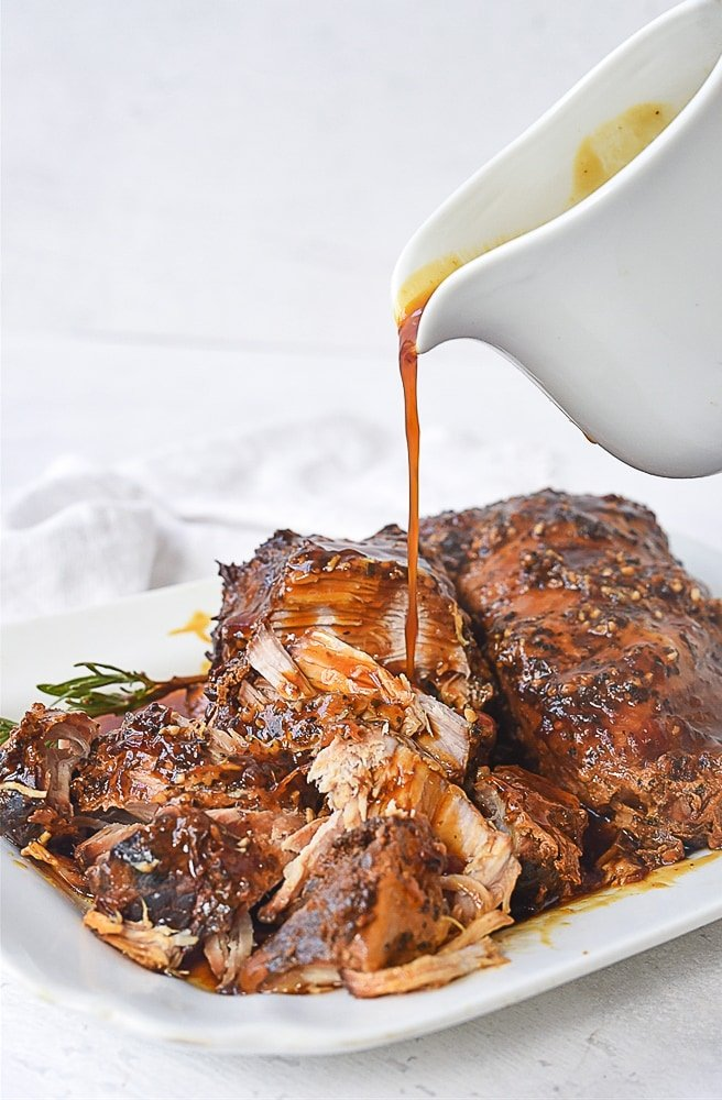 pouring sauce over pork roast