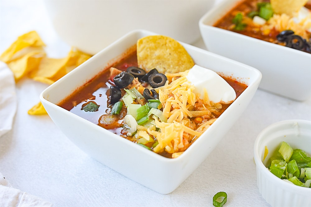 bowl of chicken tortilla soup with cheese on top