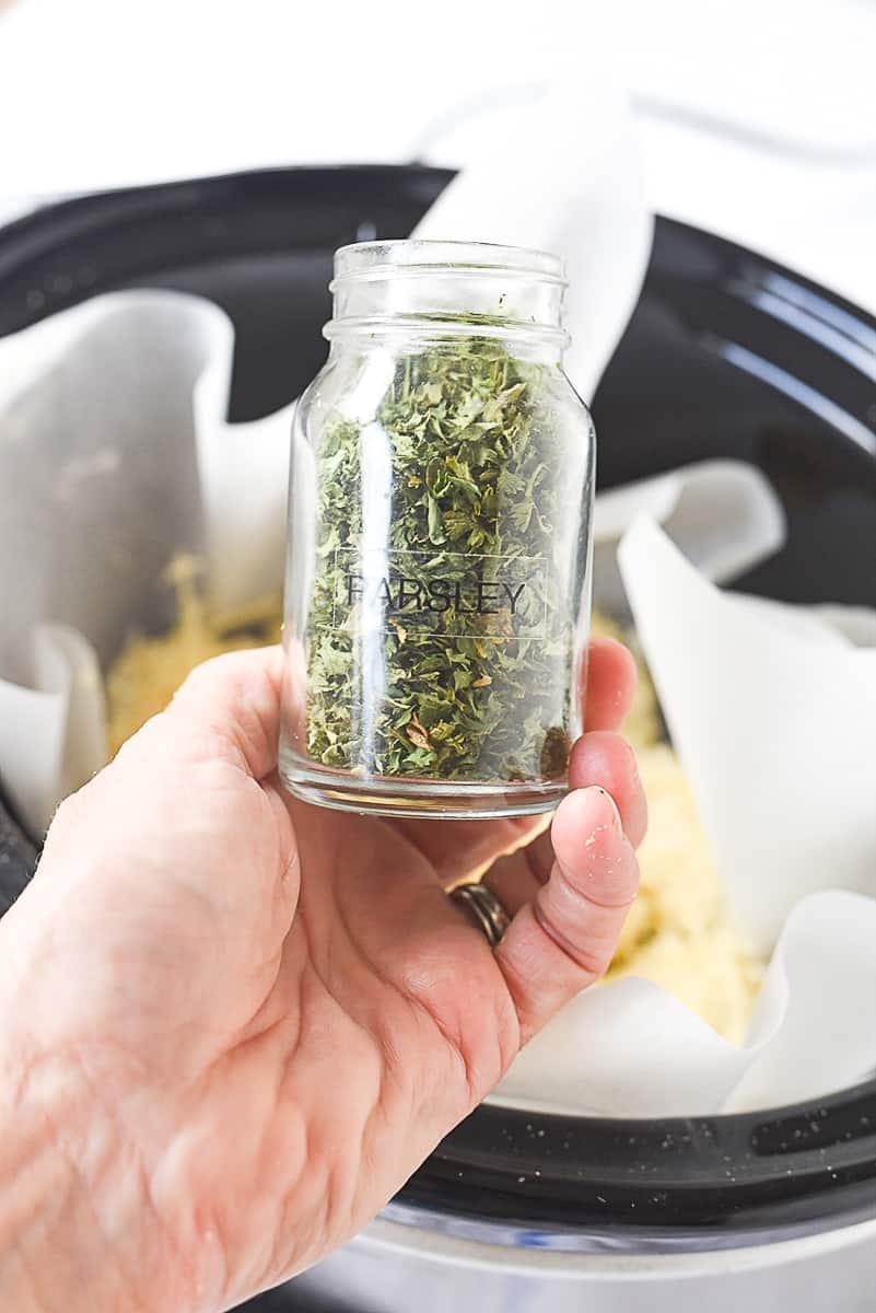 hand holding jar of parsley