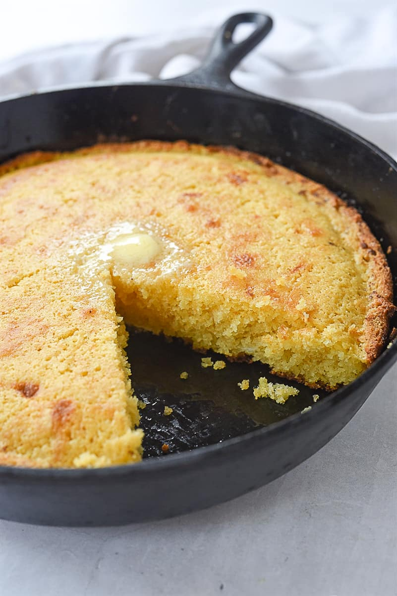 cornbread in a skillet with piece missing