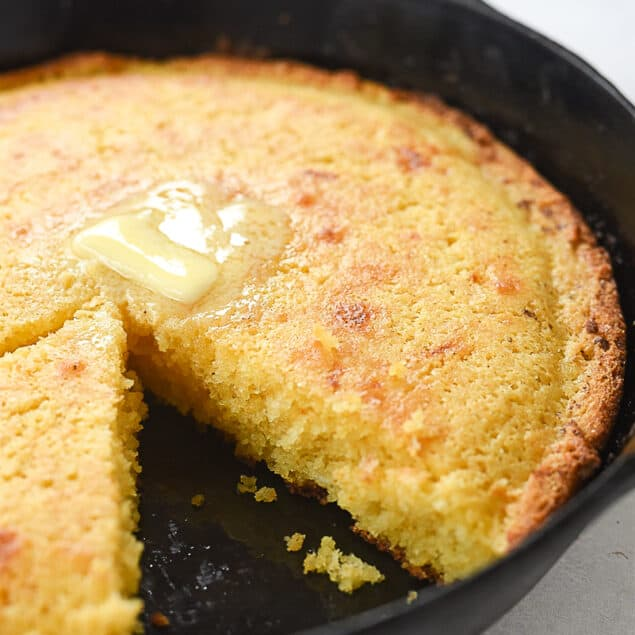 cornbread in a skillet with a piece missing