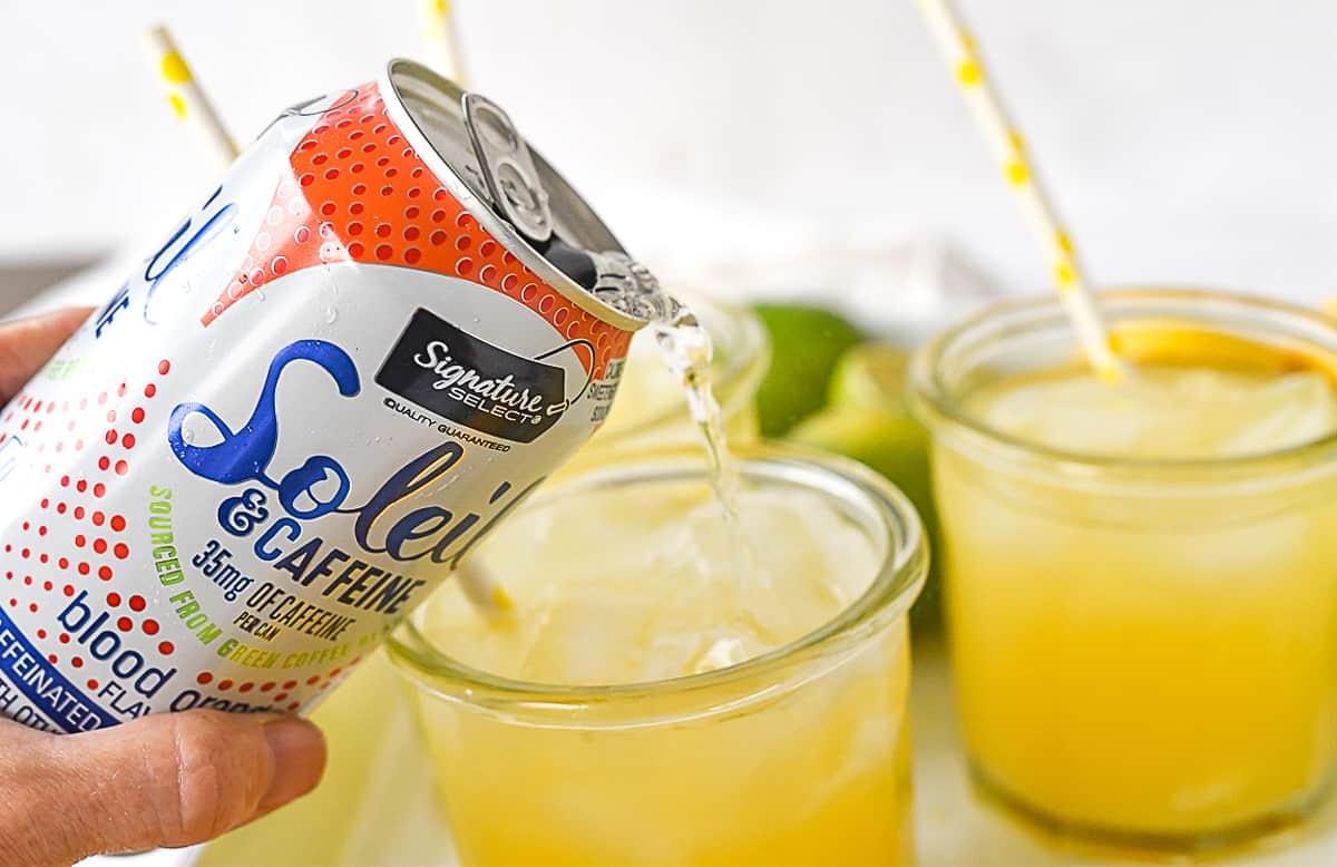 adding sparkling water to orange juice