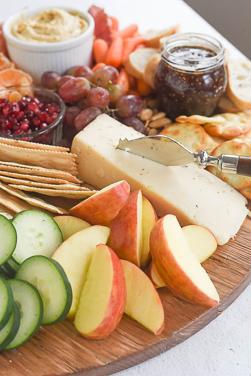 sliced apples and cucumbers on cheeses board