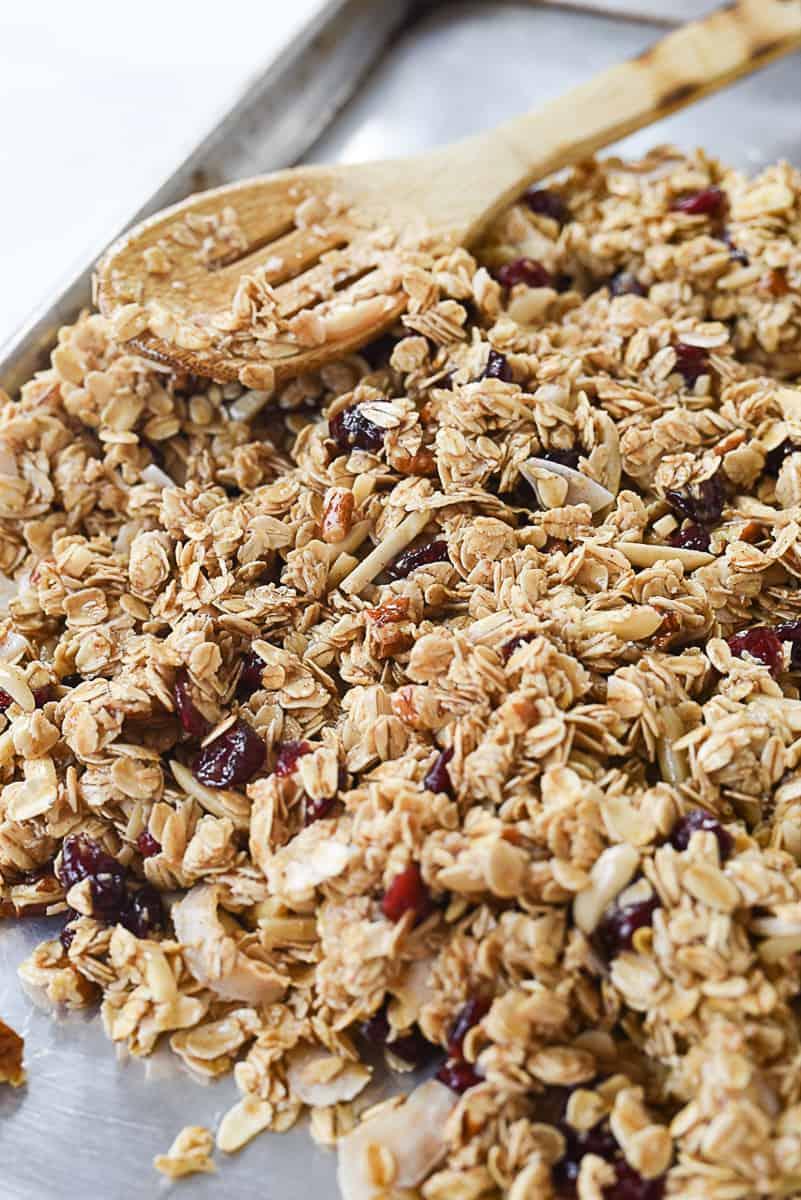 spreading granola on baking sheet