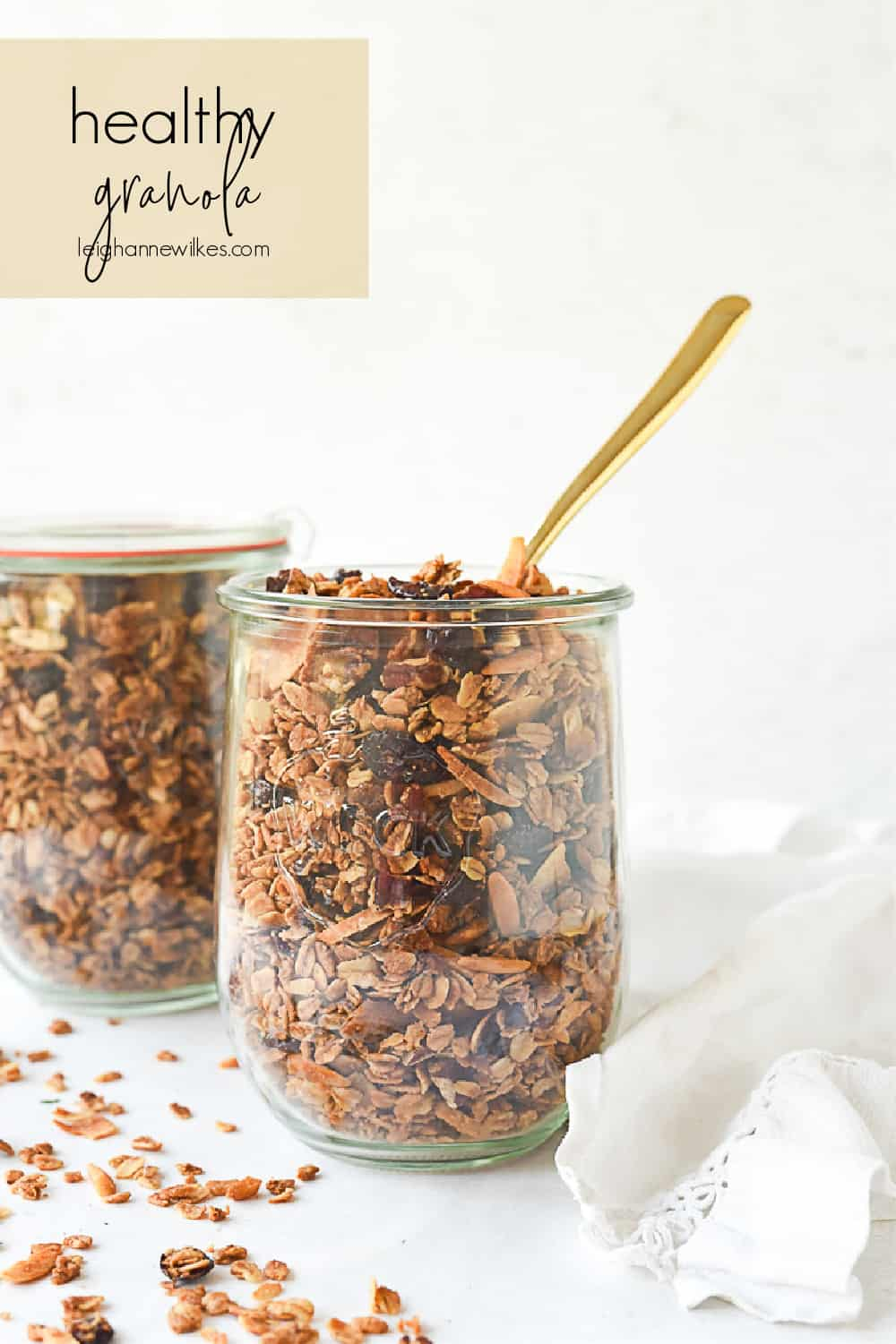 two jars of granola with a spoon in it